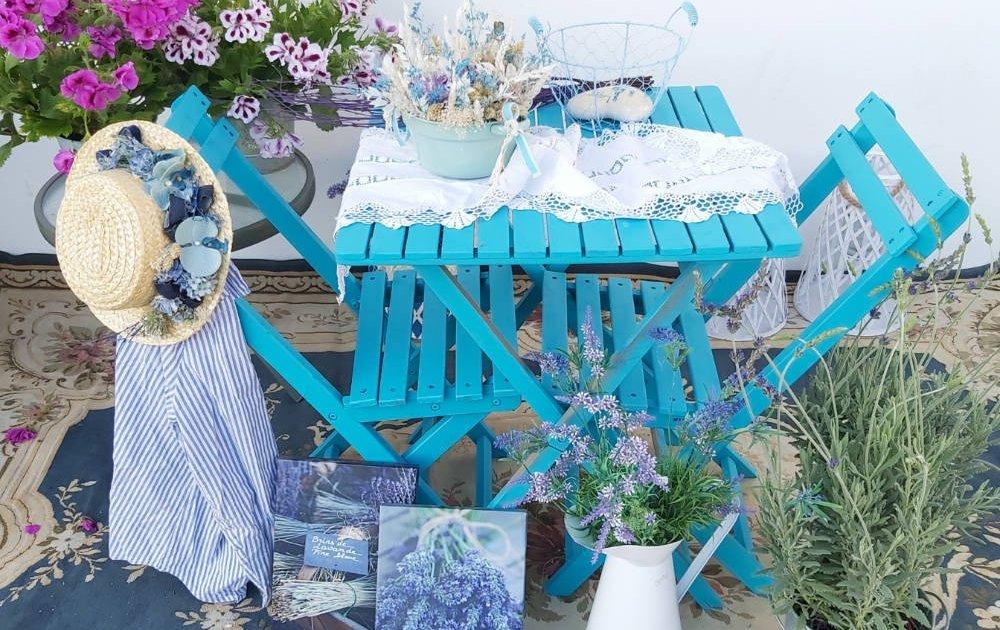 Una terrraza con muebles de madera de color azul, planta lavanda, flores preservadas, sombrero decorativo con flores y lienzos con fotografía de ramilletes de lavanda.