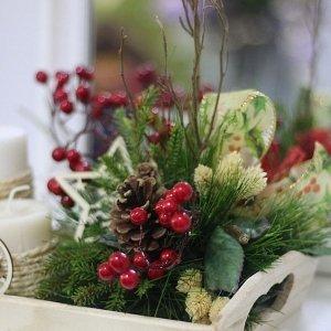 Centro navideño con ramas verdes, piñas, bayas rojas, 2 velas blancas decoradas con cordel y adornos navideños de madera