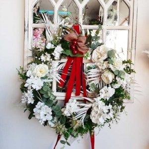 Corona de Navidad para decorar las ventanas, una base de verdes variados, flores bancas y lazos rojos navideños