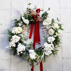 Corona navideña para decorar la puerta del hogar, símbolo de la paz con flores blancas, lazos y bolas rojas, sobre verdes variados,