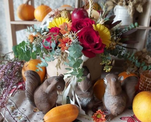 Centro de flores de colore otoñales rodeado de figuras de ardillas y pequeñas calabazas.