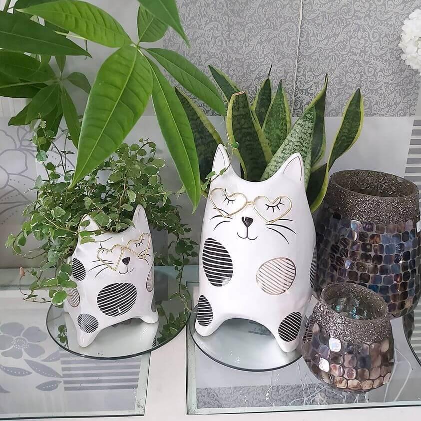 Macetas decorativas gato con plantas de interior y portavelas de cristal.