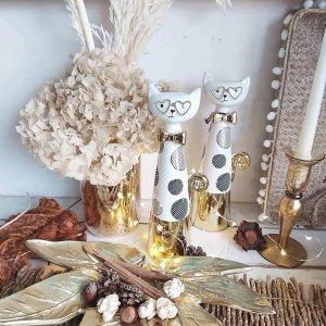Decoración moderna y otoñal con hortensias preservadas, ramas del bosque y frutos de otoño, junto a dos figuras decorativas de gatos con gafas