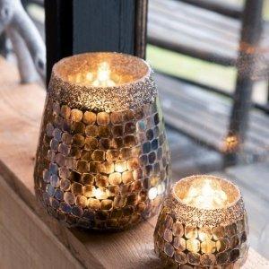 Portavelas decorativos de cristal en dos tamaños, con velas encendidas, que dan calidez a la estancia.