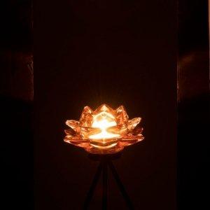 Portavelas candelabro de vidrio en forma de flor y pie de forja, iluminando en la oscuridad