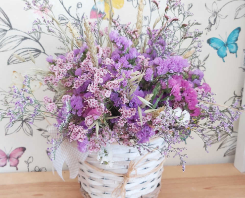 Ramo de flores naturales en maceta de mimbre, ejemplo de decoración