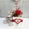 Caja con rosa eterna decorada junto a un osito de peluche para regalar en aniversarios