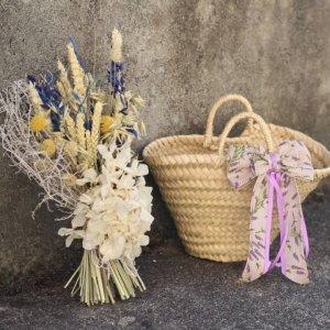 Capazo de rafia decorado con lazo lavanda y un ramillete a su lado de flores secas
