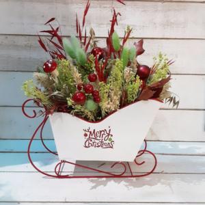 Centro de mesa original de Navidad en trineo de Papá Noel con flores secas de colores navideños