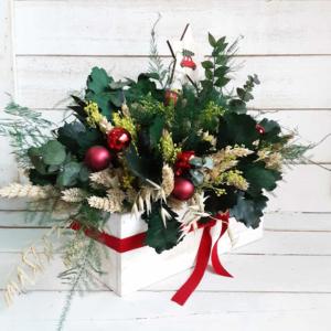 Centro navideño natural con ramas de carballo, eucalipto y flores del campo. Adornado con bolitas y pick navideño.