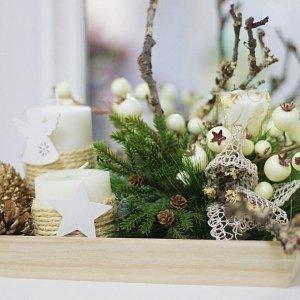 Centro para decoración de Navidad con elementos naturales como piñas y ramas del bosque, y elementos perdurables como pino y bayas de imitación, en bandeja de madera natural para una deco sostenible