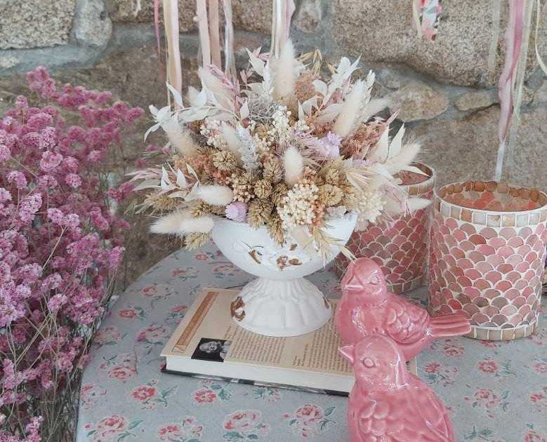 Deco inspirada en Jane Austen, un centro de flores secas del campo con detalles decorativos en tonos suaves y rosados, portavelas y figuras de pájaros
