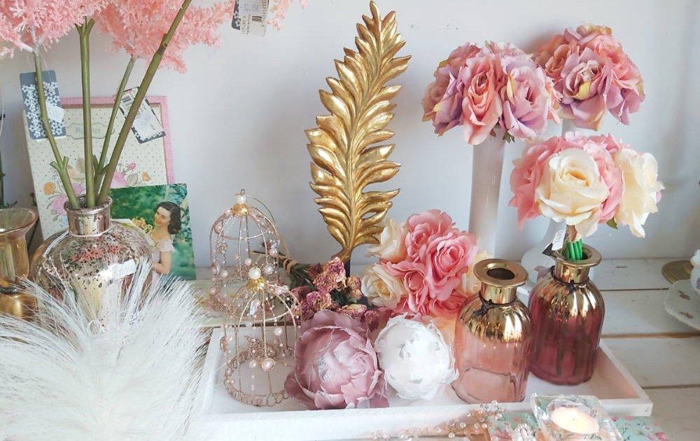 Decoración inspirada en Sentido y Sensibilidad de Jane Austen, floreros, jaulitas y flores de imitación hiperrealistas en tonos suaves, crema y rosa.