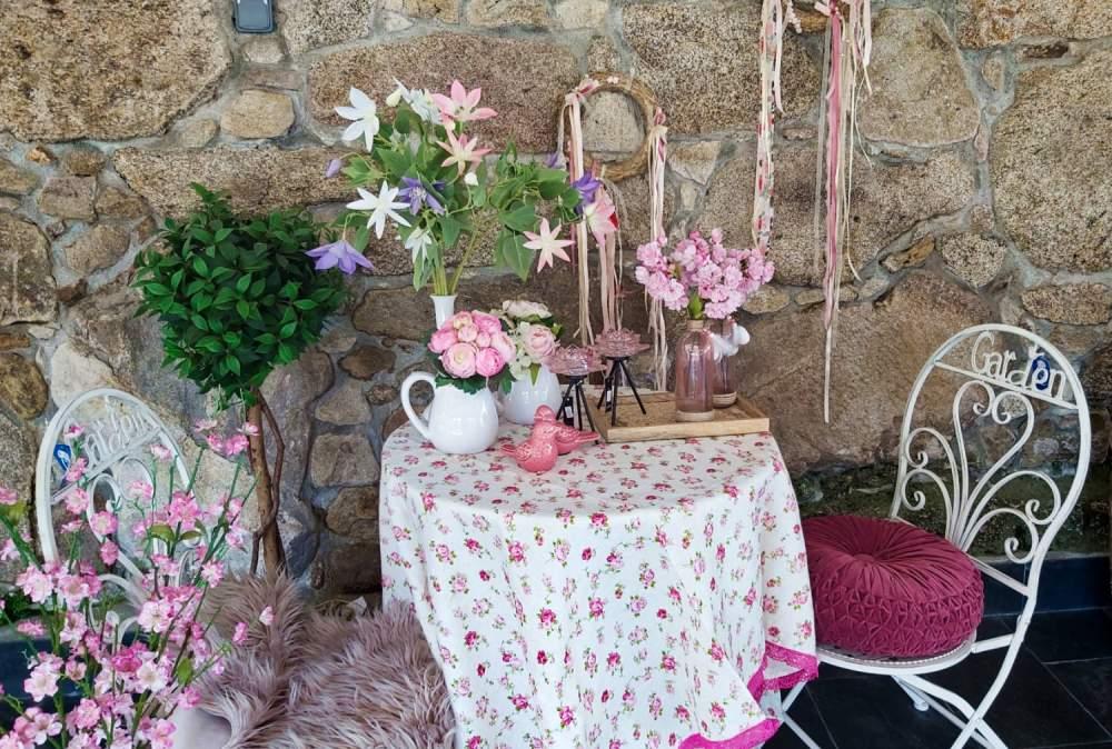 Decoración jardín interior con árboles, plantas y flores artificiales, portavelas de vidrio rosado, lecheras con flores y atrapa-sueños hechos de a mano con materiales naturales