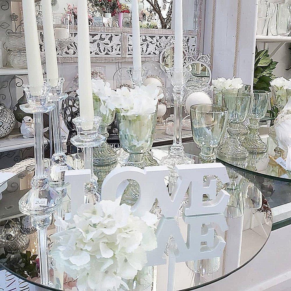 Copas de vrdrio y candelabros de cristal combinados con decoración de color blanco como las velas, las hortensias y las letras LOVE de madera