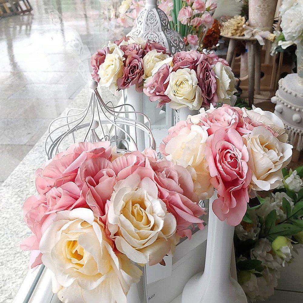 Ramilletes de rosas artificiales que parecen de verdad, en jarrones altos y estilizados de color blanco.