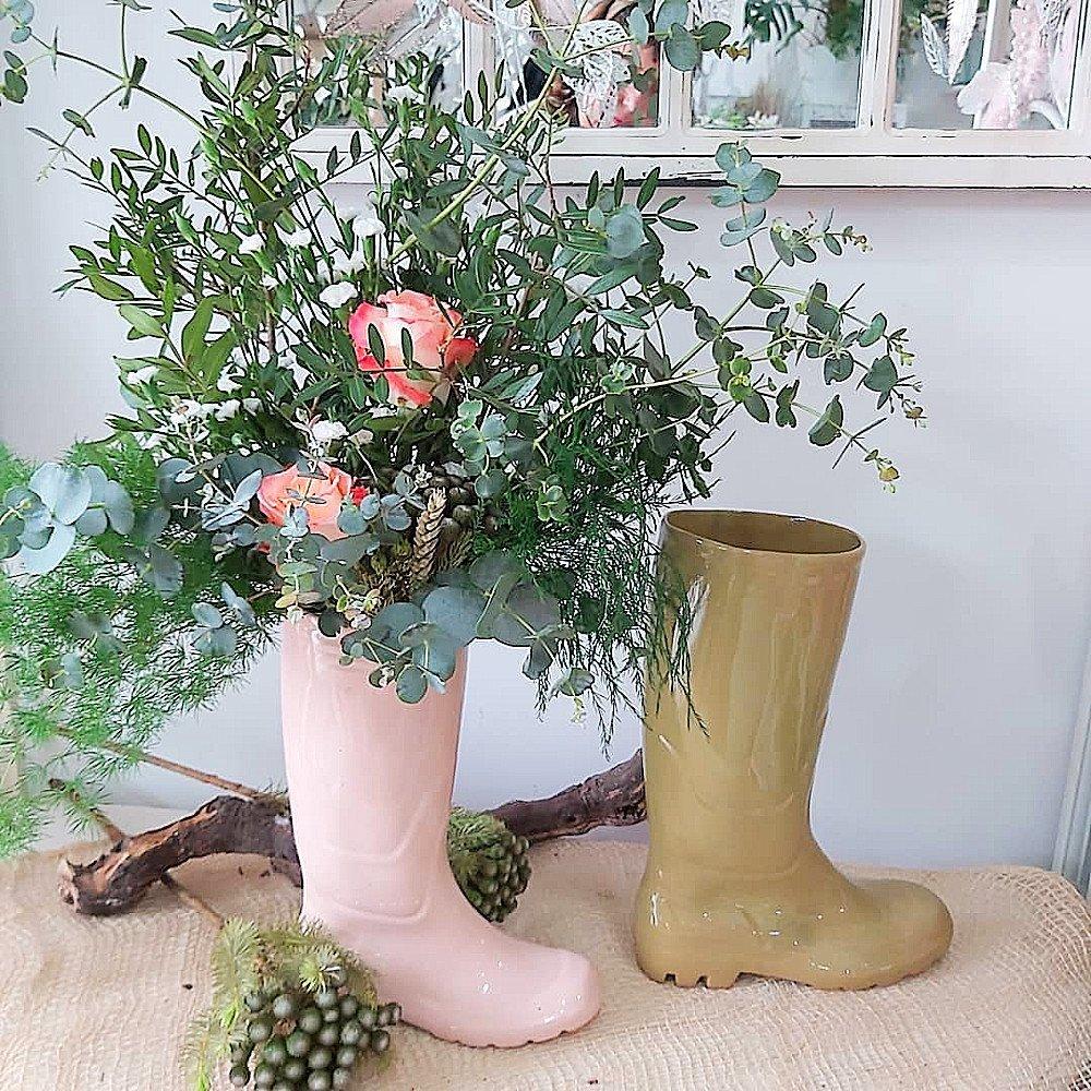 Ramo silvestre de ramajes verdes con 2 rosas. Muy vaporoso y mucho volumen con ramas de eucalipto, olivo, espigas de trigo y otros. El jarrón que lo sujeta es una original bota (tipo de la lluvia) de cerámica en color rosa.