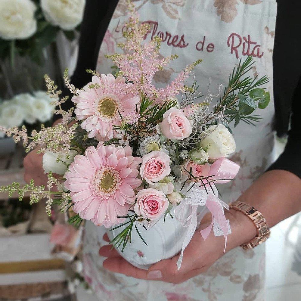 Centro de flores primaverales en tonos rosados con recipiente de cerámica blanco, sobre la mano de Nancy, equipo de las flores de Rita