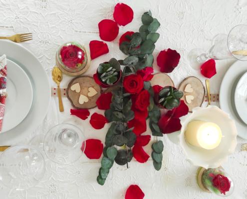 Rosas preservadas, pétalos y velas en la cena de san valentin