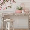 Jarrón decorativo moderno en mesa de madera rústica con detalles decorativos en tonos rosas y blancos