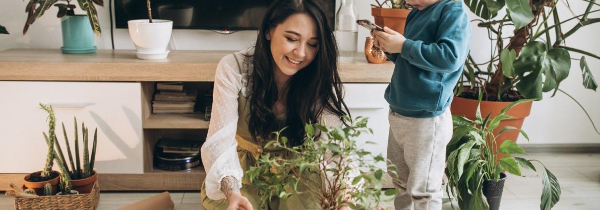 Madre con niño cultivando plantas en casa