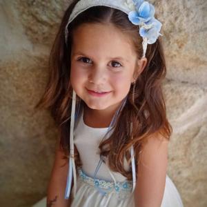 Niña sonriendo con diadema flores azules