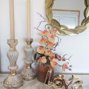 Decoración recibidor con candelabros, velas y orquídea artificial que parece de verdad.