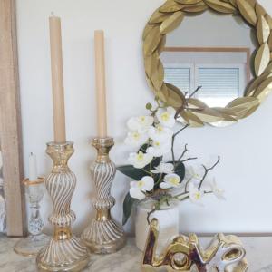 Orquídea blanca artificial que parece de verdad en decoración de hogar con espejo dorado y candelabros a juego