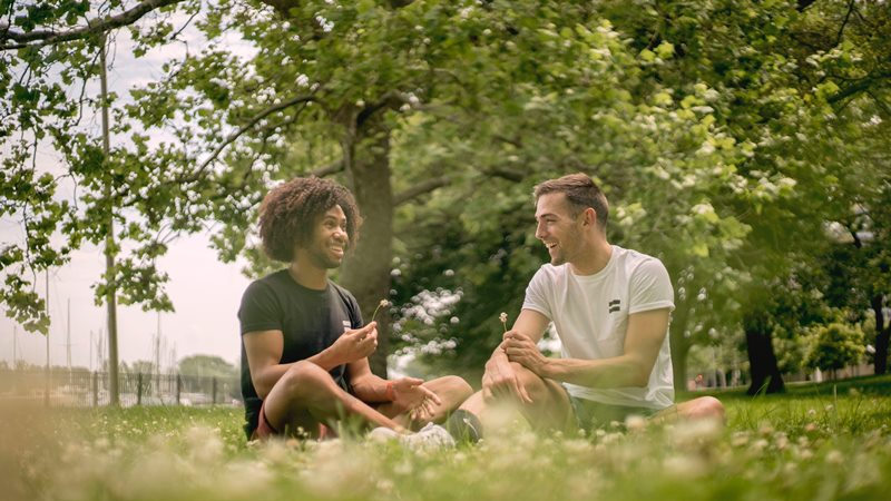 Pareja de chicos enamorados sentados sobre la hierba