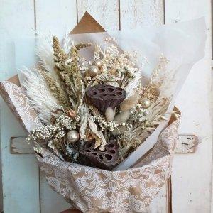 Ramo de flores en tonos nude con bolitas navideñas que se pueden retirar al terminar las fiestas. Son flores que duran muchos meses (y años). Están envueltas en papeles craft muy bonitos con preciosos lazos.