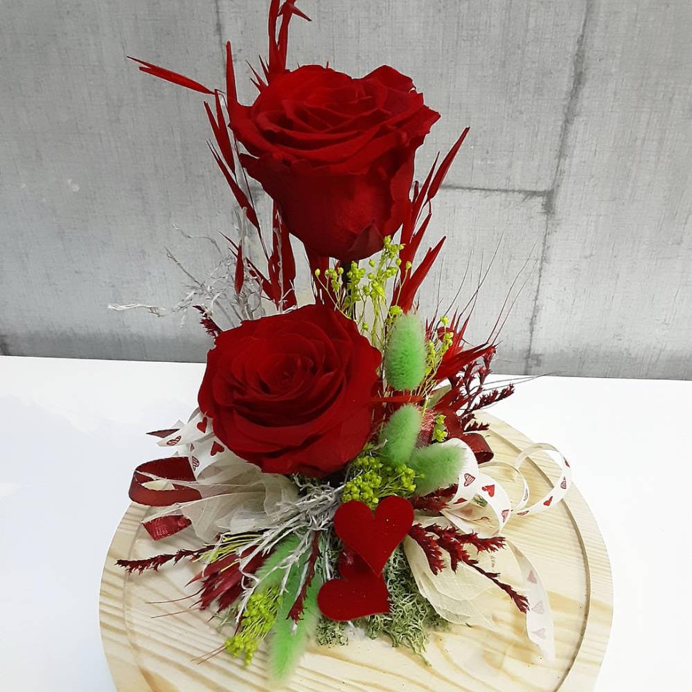 Rosa eterna en cúpula, arreglo floral de 2 rosas preservadas con flores secas de colores verde y rojo con lacitos y corazones para regalar en aniversarios.