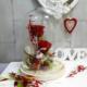 Arreglo con 2 rosas rojas preservadas y flores de secas de colores verdes y rojas en la base, en una cúpula de vidrio.