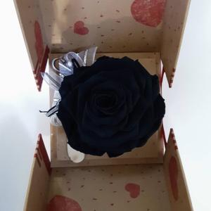 rosa eterna negra en caja que se abre para sorprender.